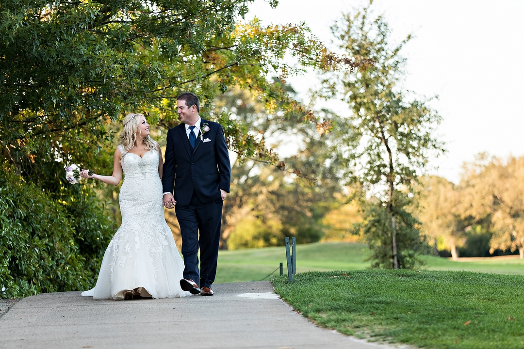 Image, taken by Siegel's Portrait Design, of bride and groom walking along paved path with golf course in background.