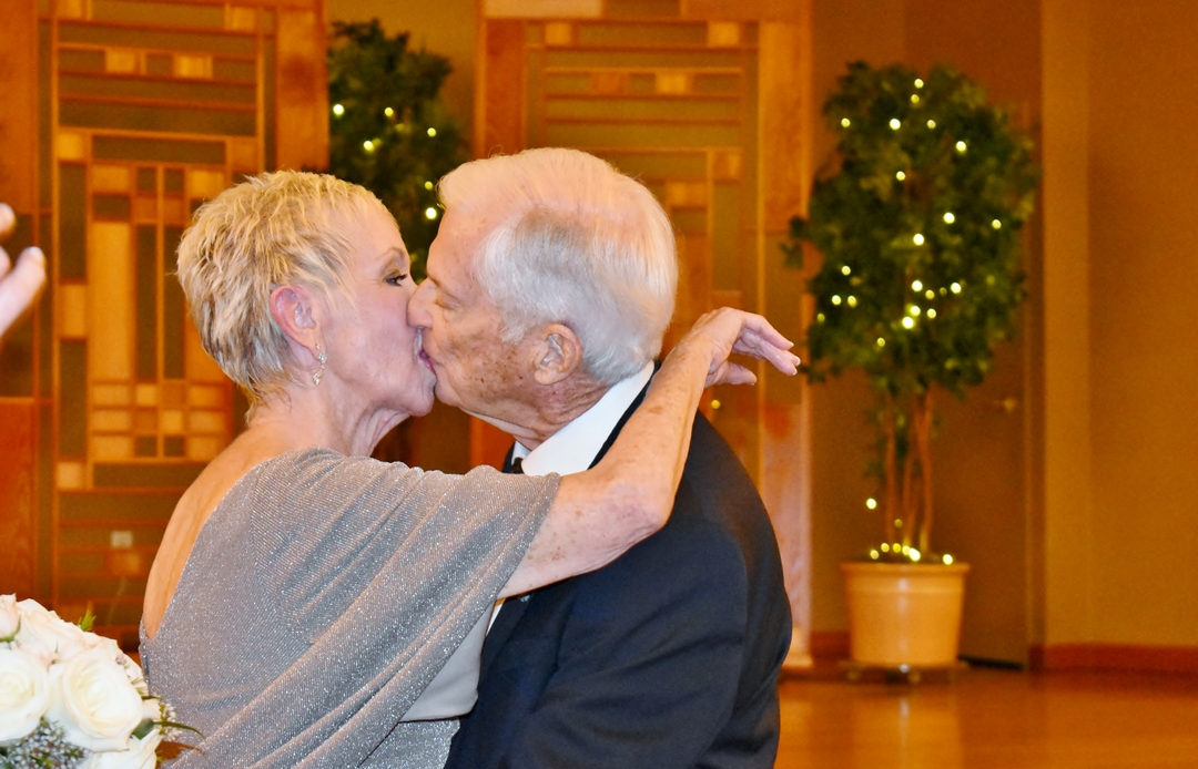 Newlywed man and woman kissing, with ballroom decor in background.