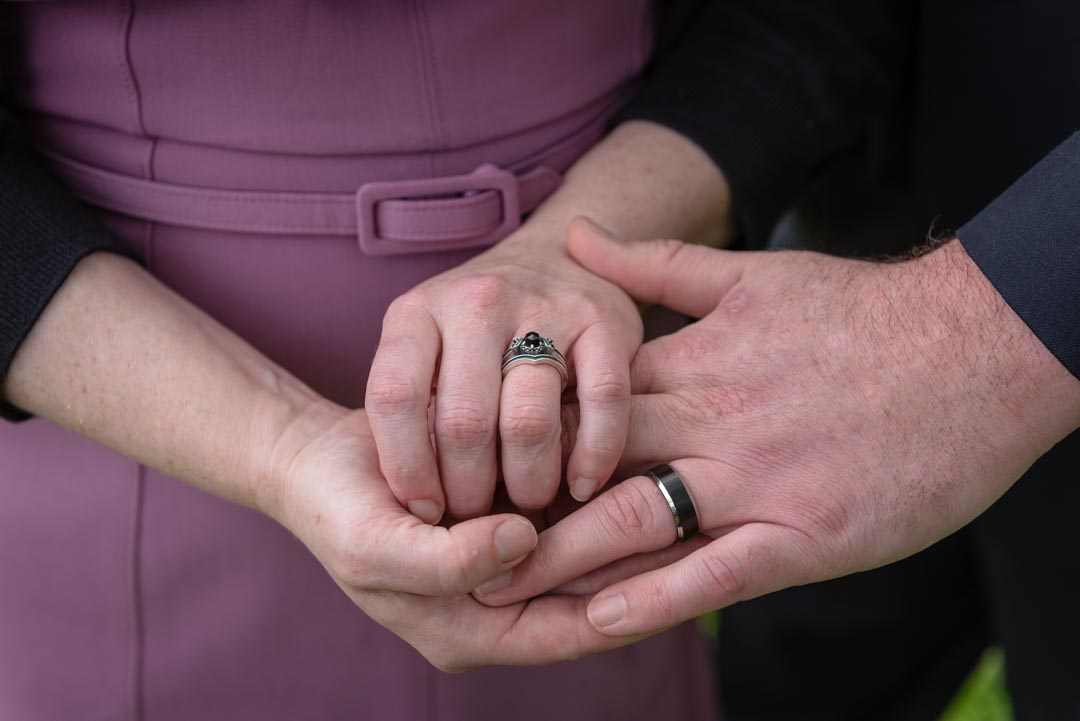 Closeup photo of the hands of a man and a woman, showing their wedding rings following their elopement ceremony.