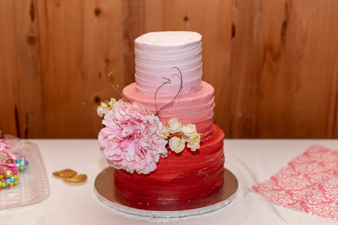 Three-tier wedding cake in shades of pink and burnt umber, with large pink flower as garnish.