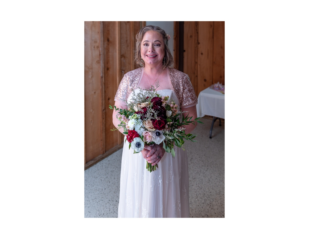 Smiling bride standing in reception hall and holding her bouquet.