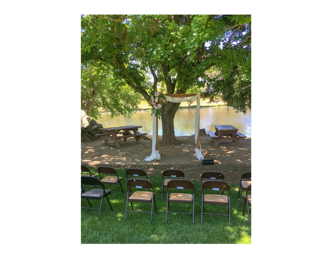 Wooden wedding arch, draped and placed under tree with water in background and folding chairs in foreground facing arch.