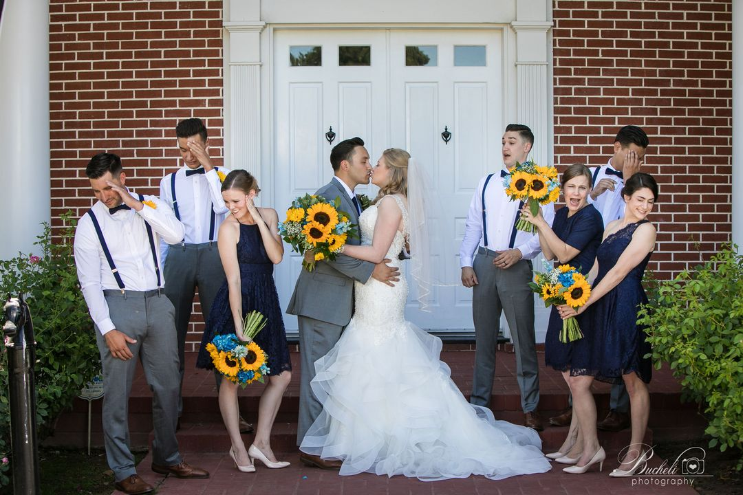 Bride and groom kissing, while bridal party pretend to grimace and look away, all standing in front of large white door and brick building.