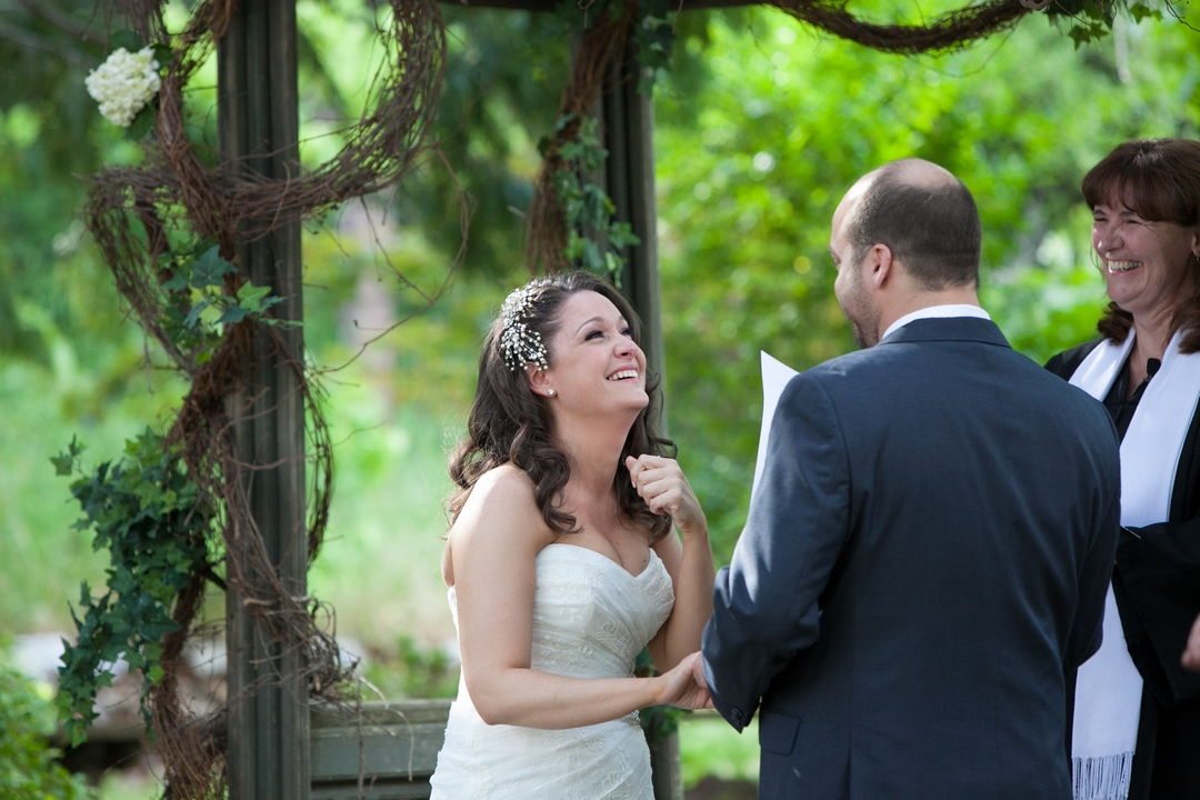 Bride looking at groom during wedding ceremony and laughing, with officiant smiling in background