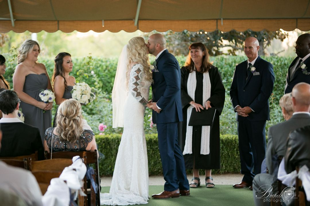 Bride and groom kissing at end of wedding ceremony, while officiant and bridal party happily look at them!