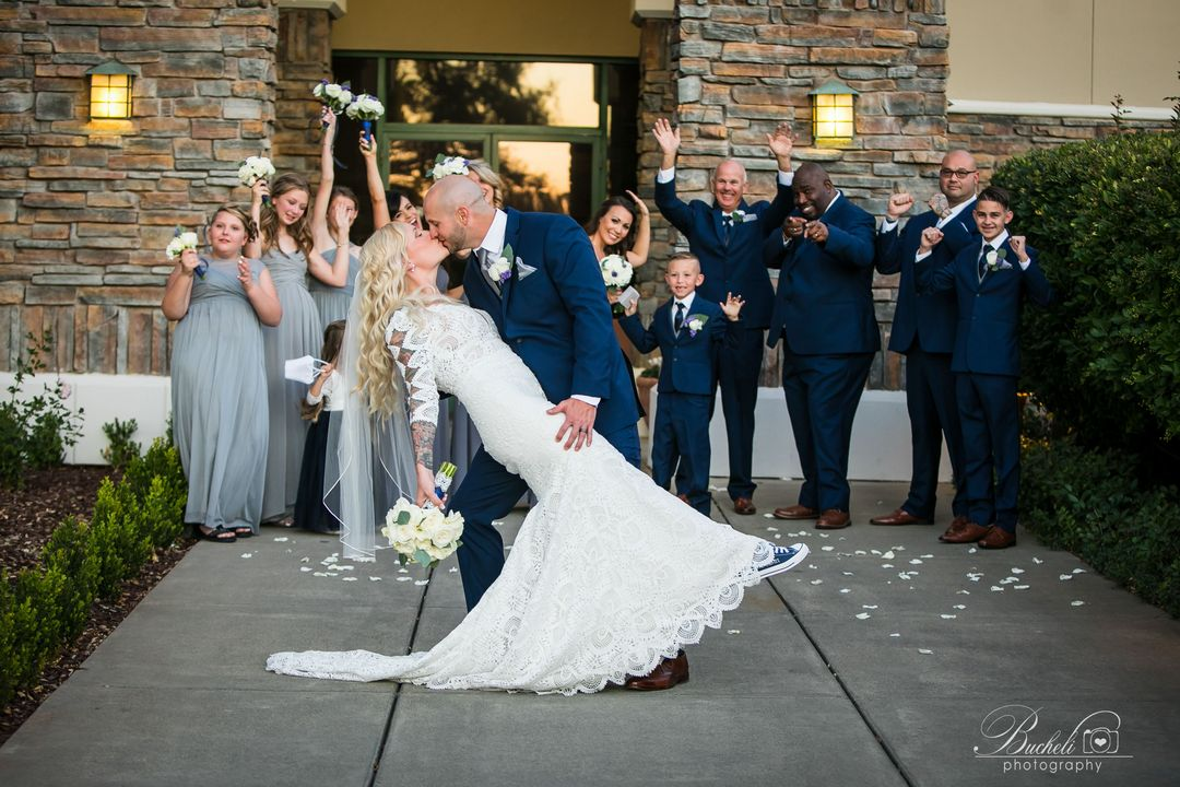 Groom dipping bride and kissing her, while bridesmaids and groomsmen watch and smile!
