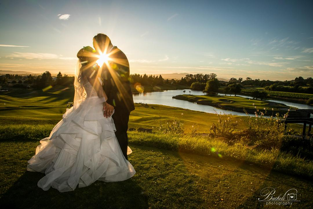 Bride and groom kissing, with sunset starburst between them and a river landscape behind them.