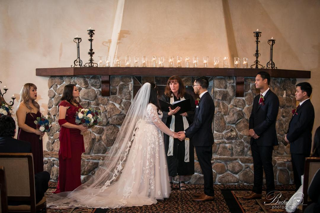 Bride and groom holding hands and listening to wedding ceremony presented by officiant, who is standing in front of large brick fireplace at Catta Verdera Country Club.
