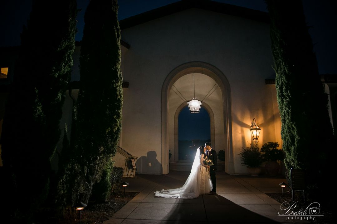 Nighttime image of bride and groom kissing near the fountain at Catta Verdera Country Club.