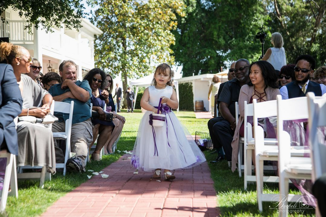 Flower girl walking down garden brick aisle, with smiling wedding guests sitting on either side.