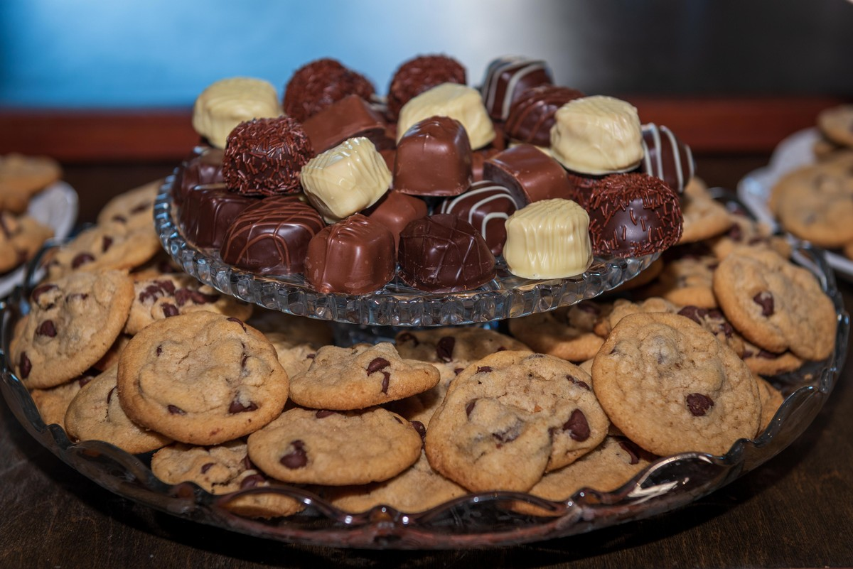 Two-tiered dessert platter, with homemade chocolate chip cookies on the bottom row and assorted chocolate candies on the top row.