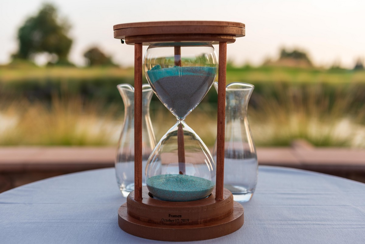 Wooden hourglass with teal and grey sand, used for sand blending ritual during wedding ceremony.