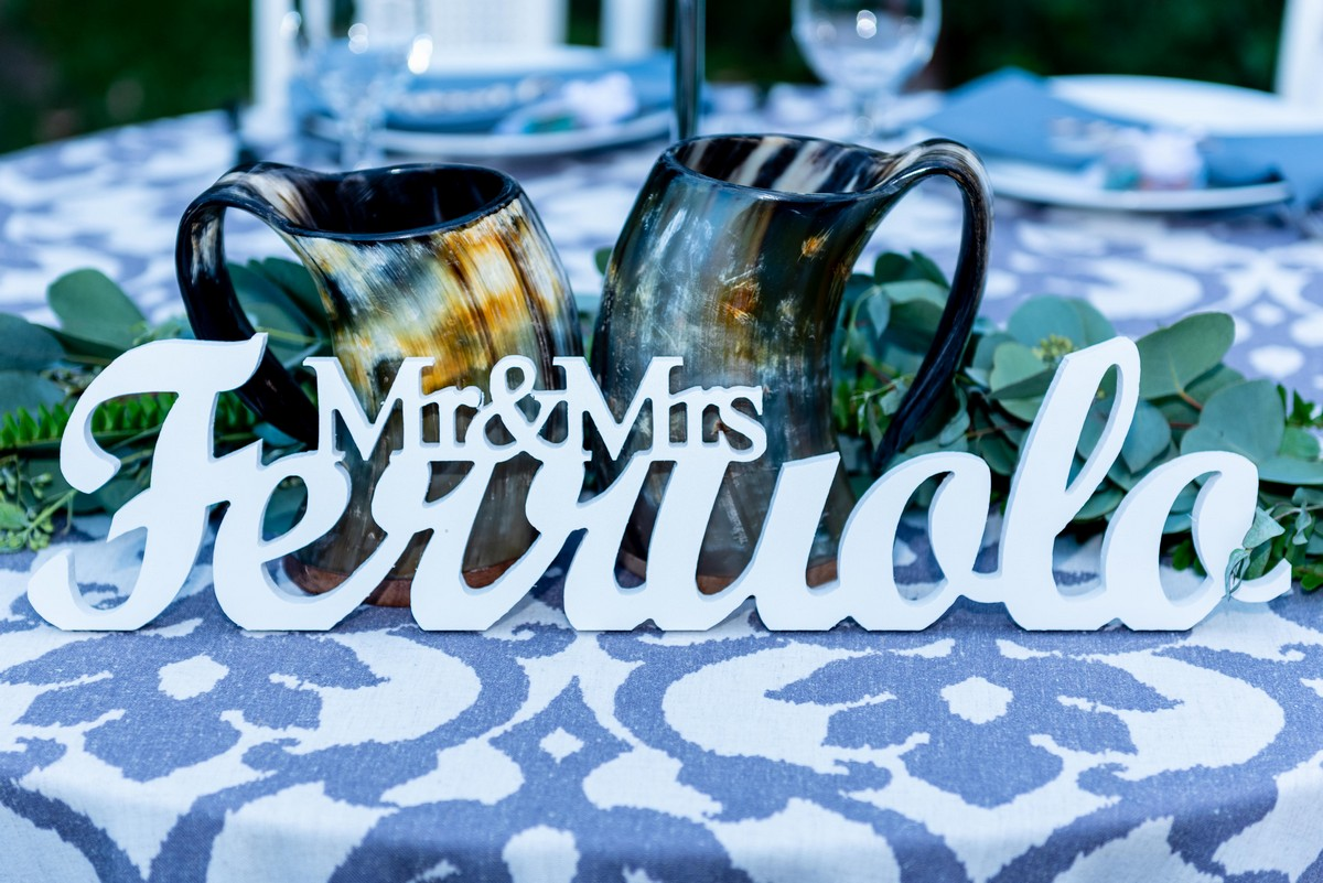 """Two curved metal toasting cups, placed on a table behind a sign stating """"Mr. and Mrs. Ferruolo."""""""